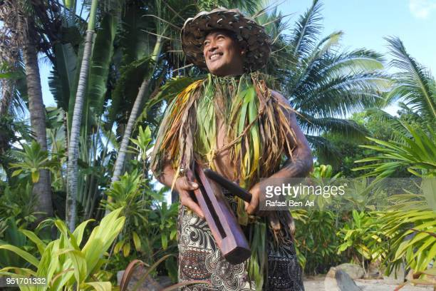 Pacific Islander man plays music on a small Pate wooden stick drum instrument in Rarotonga Cook Islands