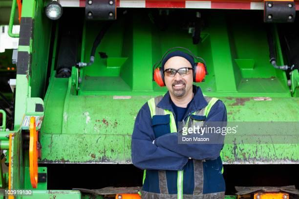 pacific islander man standing by garbage truck - eboueur photos et images de collection