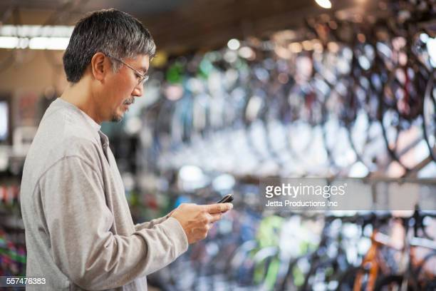 Pacific Islander man texting on cell phone in bicycle shop