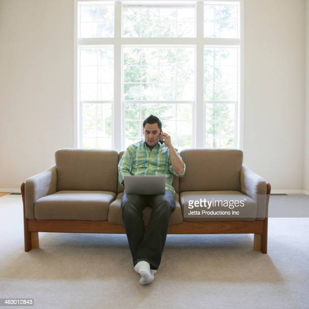 Pacific Islander man using laptop and cell phone