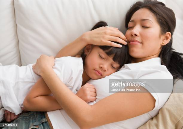 Pacific Islander mother and daughter sleeping