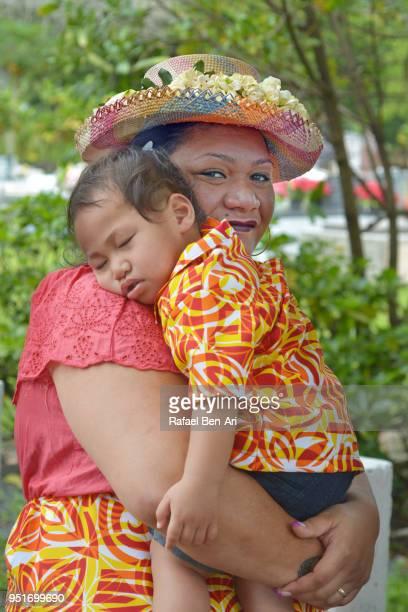 pacific islander mother carry her  sleeping boy on her arms - rafael ben ari fotografías e imágenes de stock