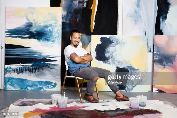 Pacific Islander painter admiring canvas on floor