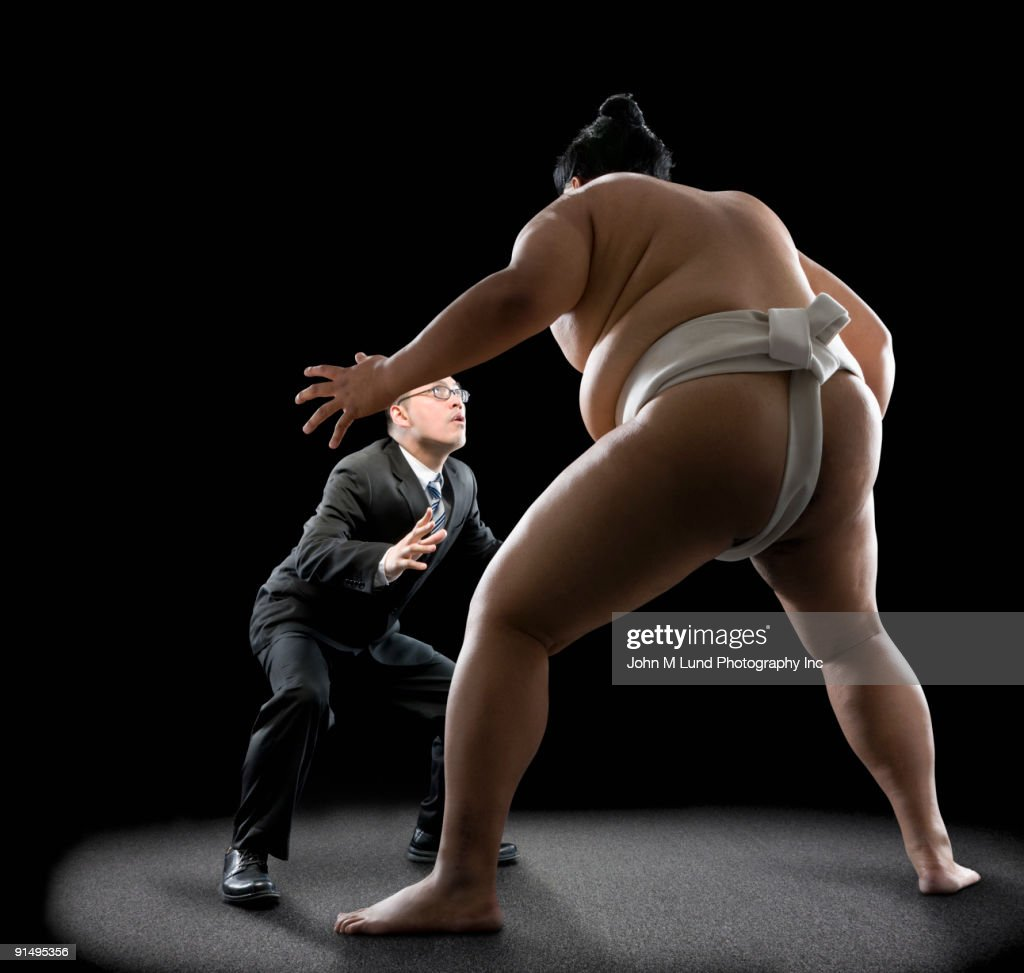 Pacific Islander sumo wrestler challenging businessman : Stock Photo