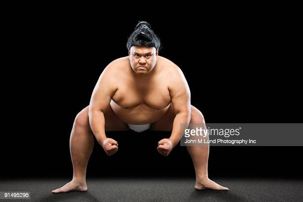 Pacific Islander sumo wrestler crouching with clenched fists