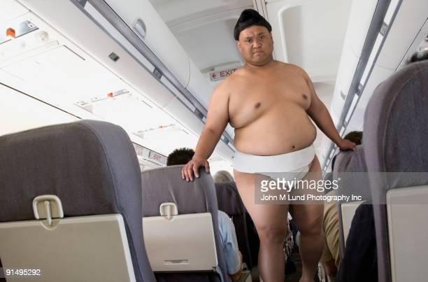 pacific islander sumo wrestler walking down airplane aisle - vechtsport stockfoto's en -beelden