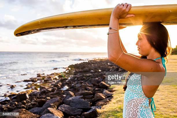 Pacific Islander surfer carrying surfboard on rocky beach