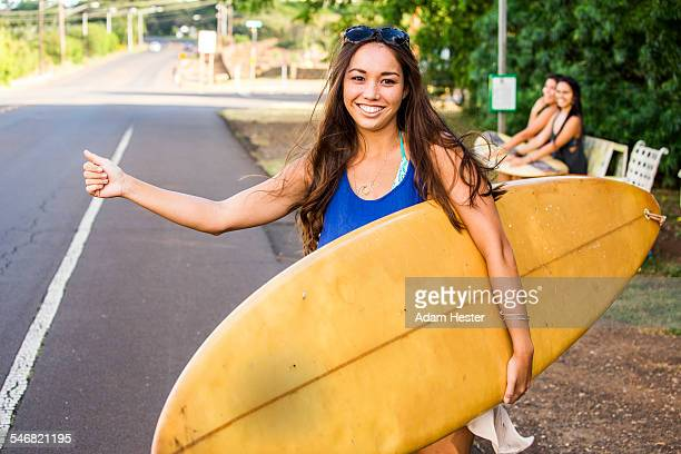 Pacific Islander surfer hitch hiking on rural road