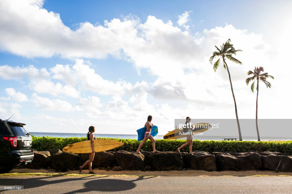 Pacific Islander surfers carrying surfboards on rock wall : Stock Photo