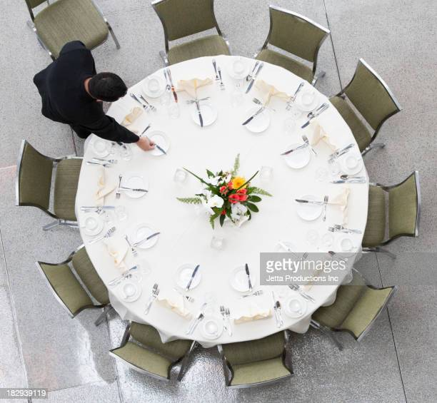 Pacific Islander waiter setting table in dining room