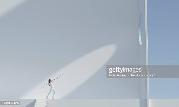 pacific islander woman aiming javelin at hole high on wall - aiming stock pictures, royalty-free photos & images