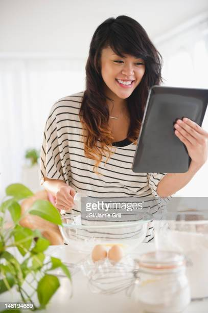Pacific islander woman baking and using digital tablet