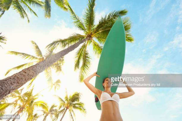 pacific islander woman balancing surfboard on head under palm tree - waikiki stock pictures, royalty-free photos & images
