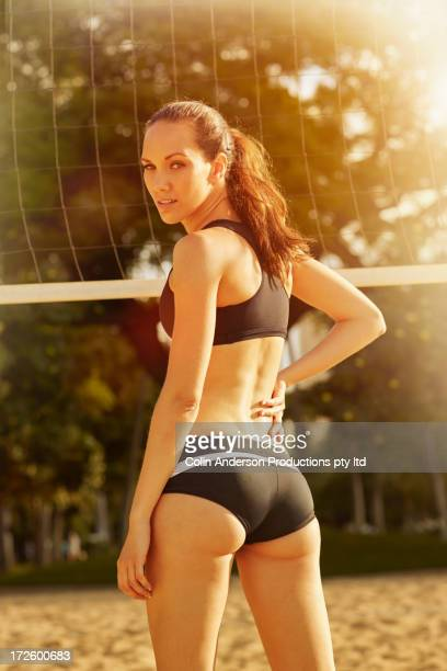 pacific islander woman by volleyball net - womens volleyball stock photos and pictures