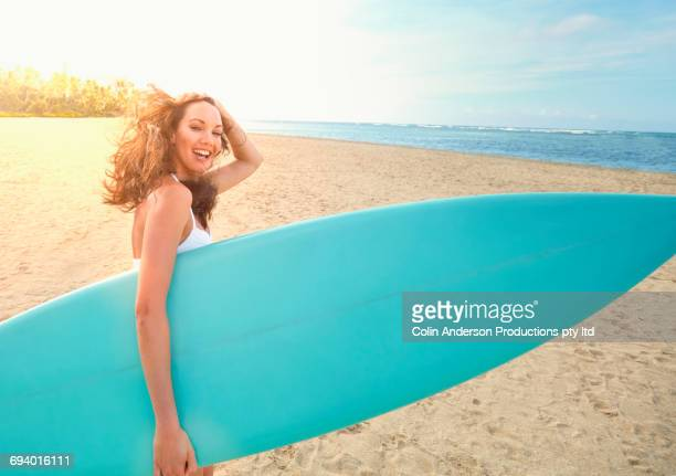 Pacific Islander woman carrying surfboard on beach