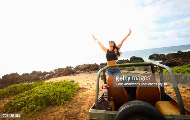 Pacific Islander woman celebrating in off-road vehicle