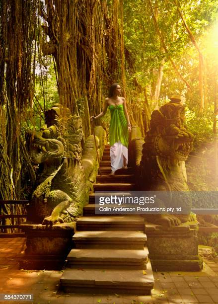 Pacific Islander woman descending staircase of ornate ruins