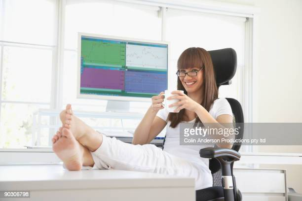 Pacific Islander woman drinking coffee at desk with feet up