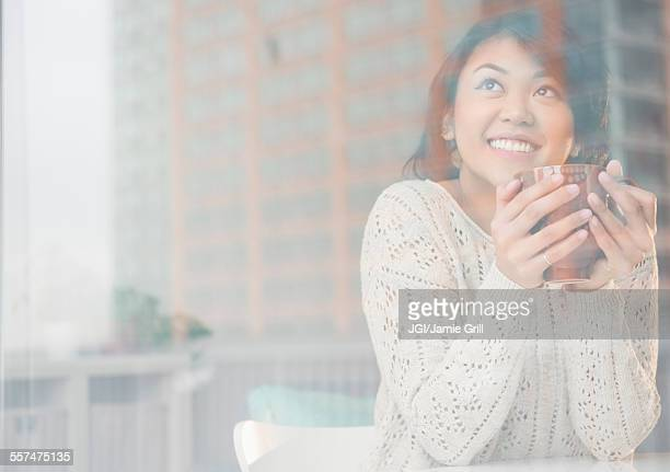 Pacific Islander woman drinking cup of coffee behind window