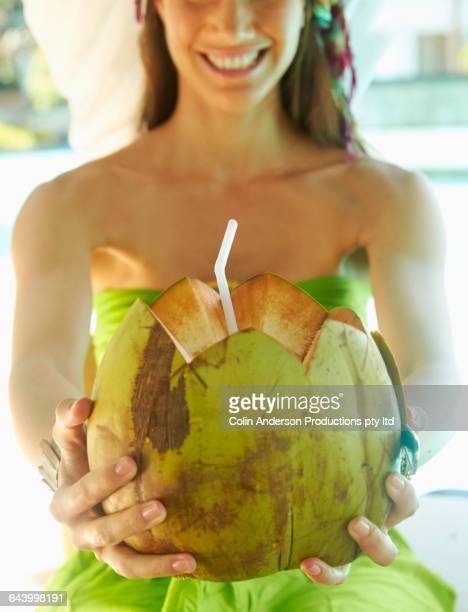 Pacific Islander woman drinking fresh coconut