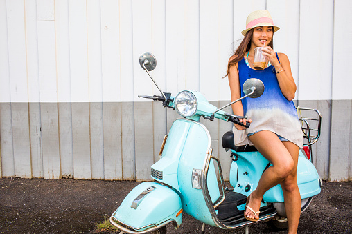 Pacific Islander woman drinking iced coffee on scooter - gettyimageskorea