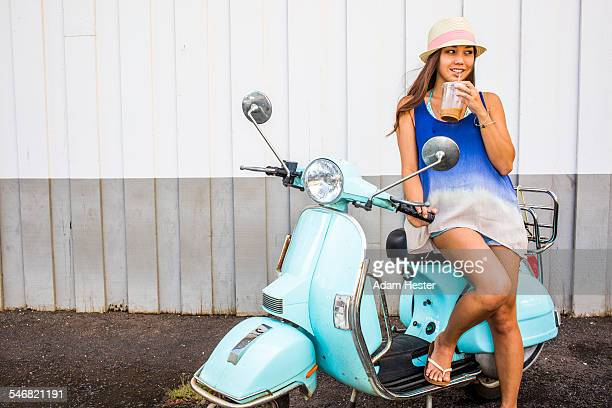 pacific islander woman drinking iced coffee on scooter - moped stock photos and pictures