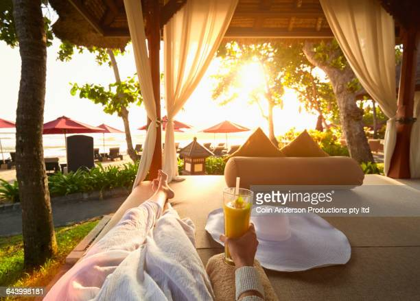 Pacific Islander woman drinking juice in gazebo