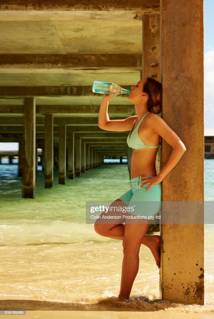 Pacific Islander woman drinking water under wooden pier on beach : Foto stock