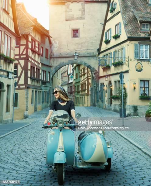 Pacific Islander woman driving vintage scooter in village