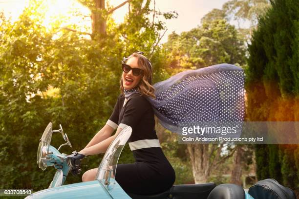 Pacific Islander woman driving vintage scooter