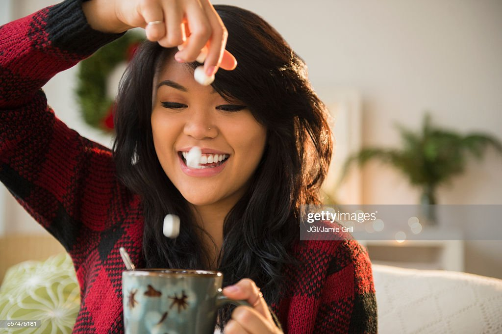 Pacific Islander woman dropping marshmallows into hot chocolate : Stock Photo