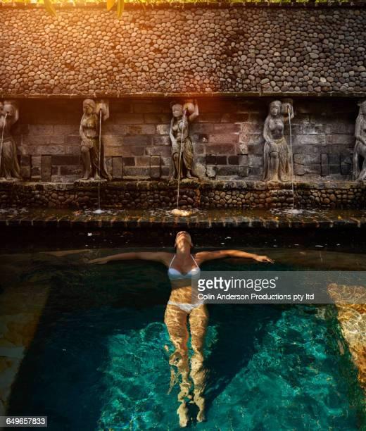 Pacific Islander woman floating in ornate pool