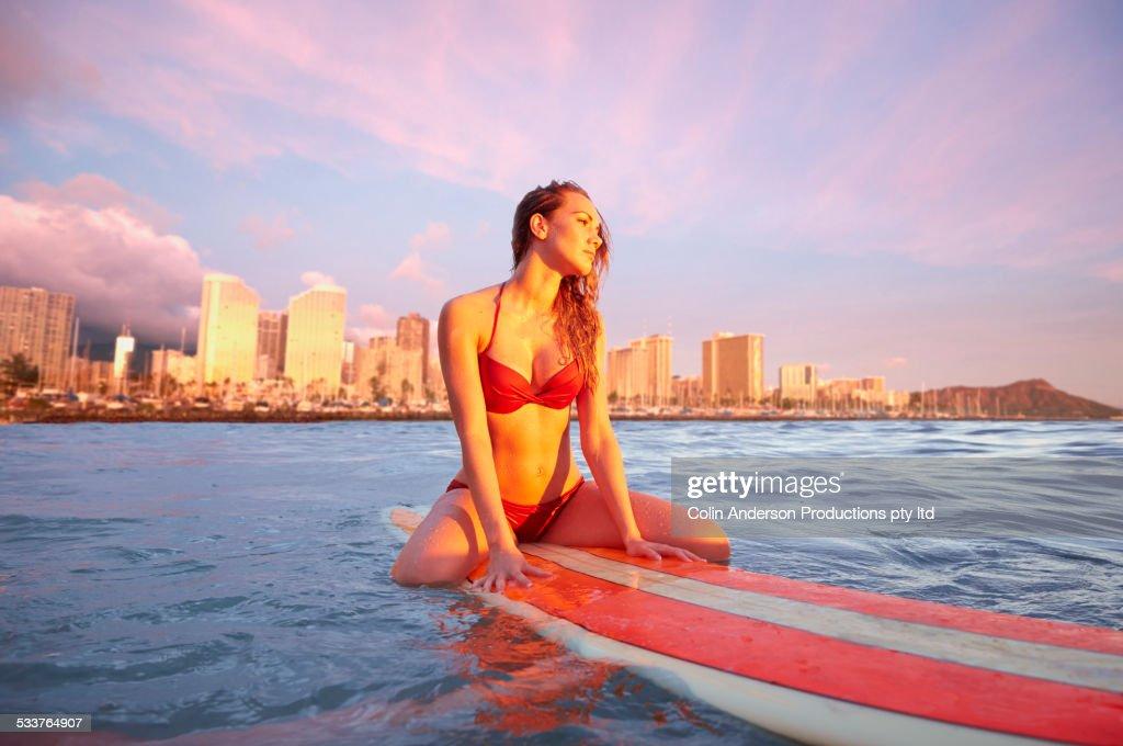 Pacific Islander woman floating on surfboard in ocean : Foto stock