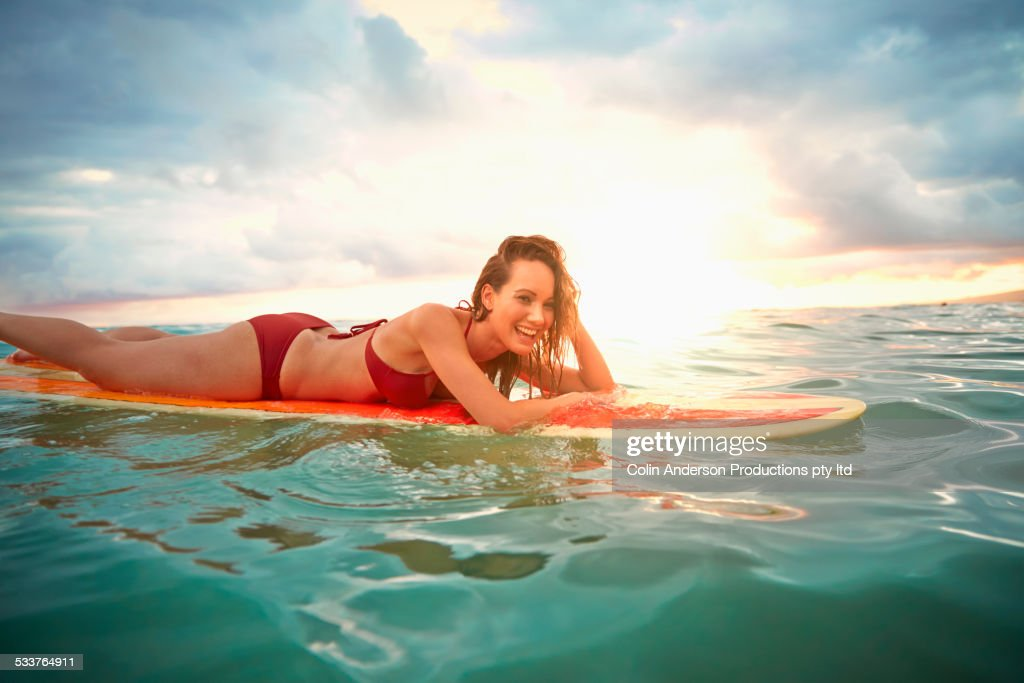 Pacific Islander woman floating on surfboard in ocean : Foto stock