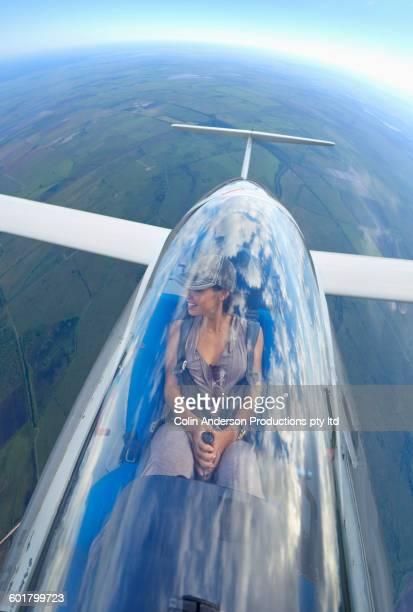 Pacific Islander woman flying glider airplane