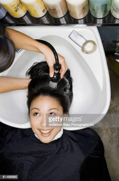 Pacific Islander woman having hair washed at salon