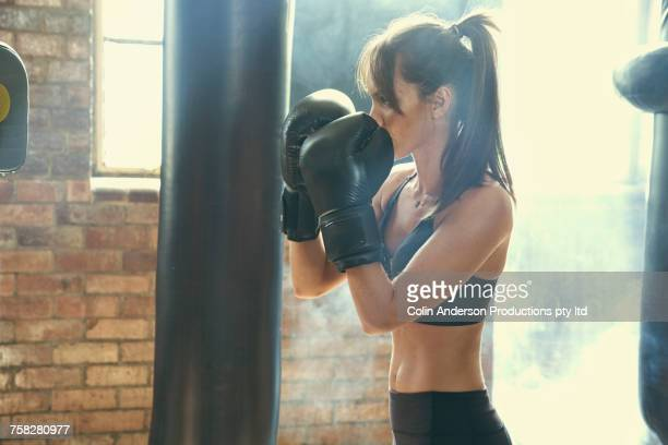 Pacific Islander woman hitting punching bag in gymnasium