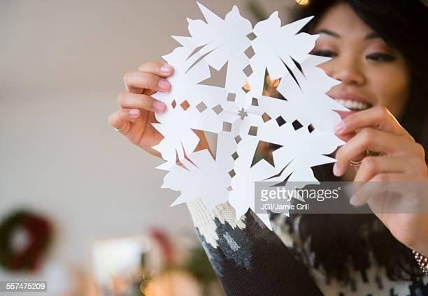 Pacific Islander woman holding paper snowflake