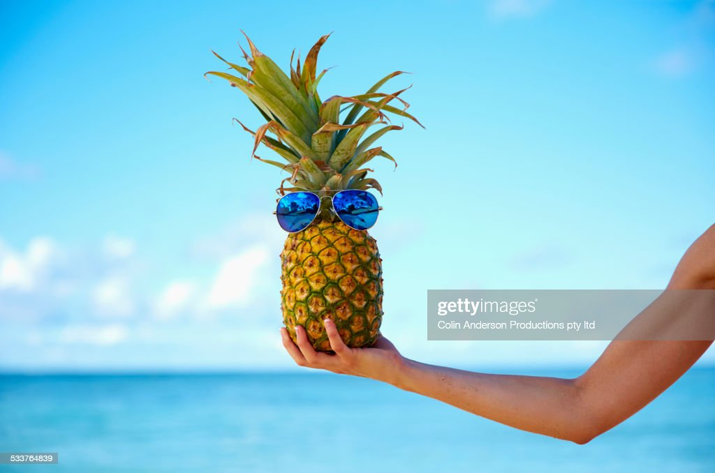 Pacific Islander woman holding pineapple with sunglasses : Foto stock