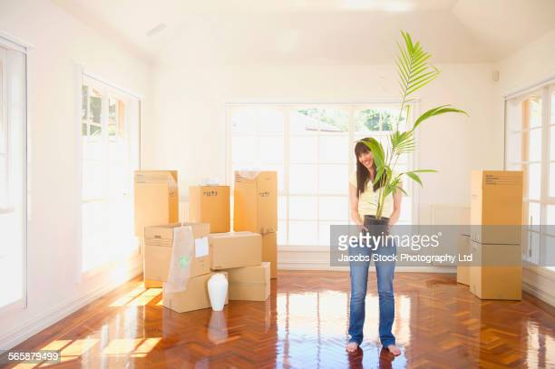 Pacific Islander woman holding potted plant in new home