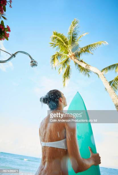 Pacific Islander woman holding surfboard and showering at beach