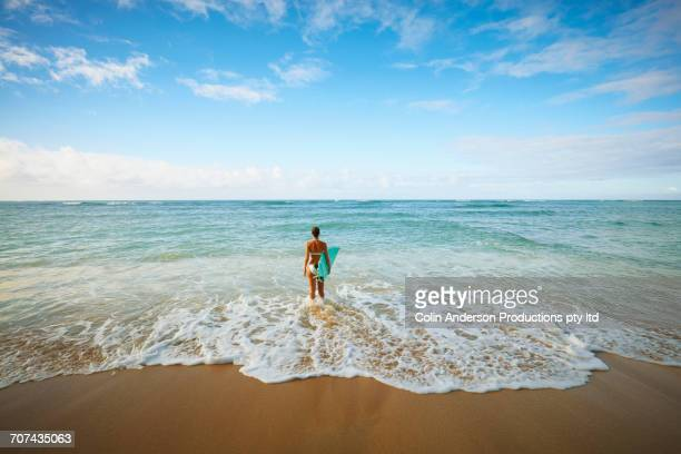 Pacific Islander woman holding surfboard in waves at beach
