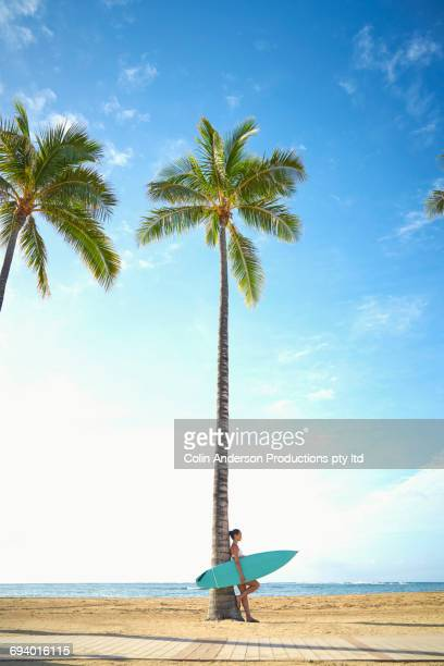 Pacific Islander woman holding surfboard leaning on palm tree
