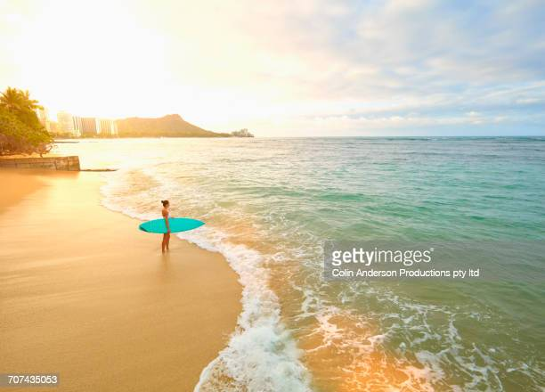 Pacific Islander woman holding surfboard on beach