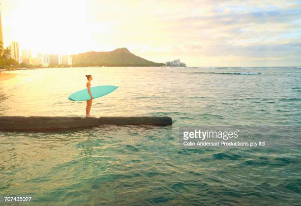 Pacific Islander woman holding surfboard on jetty