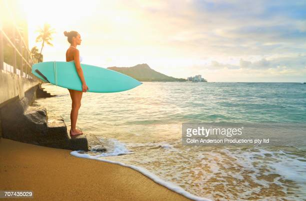 pacific islander woman holding surfboard on staircase at ocean - pacific islands stock pictures, royalty-free photos & images