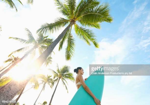 Pacific Islander woman holding surfboard under palm tree