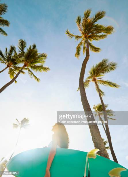 Pacific Islander woman holding surfboard under palm trees