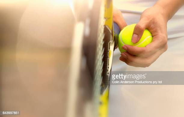 Pacific Islander woman holding tennis ball