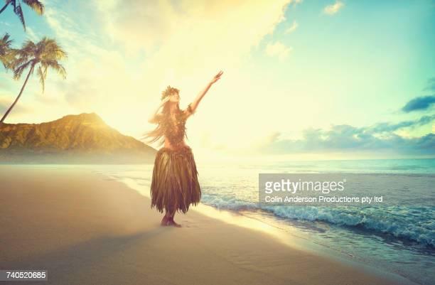 Pacific Islander woman hula dancing on beach